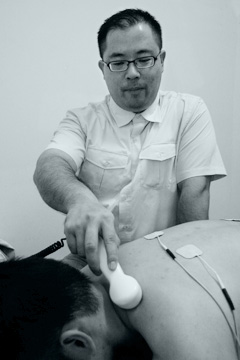 photo of chiropractor performing ultrasound treatment of neck pain